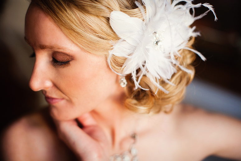 close up of a bride with a beautiful feather hair piece for her wedding day style